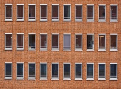 Monotonous facade of red bricks of a high-rise office building with long rectangular windows without curtains in the city center