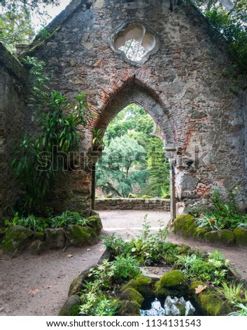 Monserrate Palace Gardens with archway through ruin stone wall.