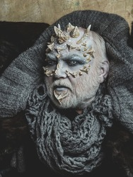Monster face with white eyes, sharp thorns and warts. Demon head with grey collar on abstract beige wall. Horror and fantasy concept. Alien or sorcerer makeup. Man with dragon skin and beard.