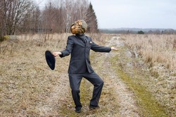 monstrous Scarecrow with a Halloween pumpkin on his head shows off and dances on a country road dressed up in a business suit