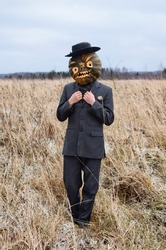 monstrous Scarecrow with a Halloween pumpkin on his head stands in a wild field dressed in a business suit