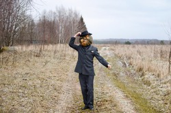 monstrous Scarecrow with a Halloween pumpkin on its head stands on a rural road dressed up in a business suit and scares passersby by greeting them