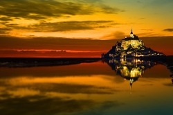 Mont Saint Michel abbey reflected in the bay at sunset, France