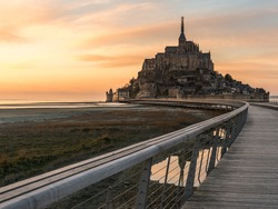 Mont saint michel at Sunset in Summer Low Tide from the bridge with reflection, France
