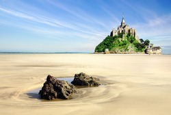 Mont Saint Michel with boulders in the foreground.