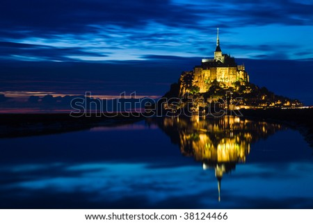Mont St. Michel reflected in the sea at night - stock photo