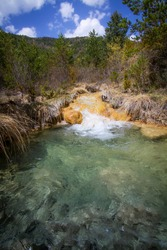 montain river on a bed of yellow stones and dry grasses, flows into a river pool of crystalline waters, Sorradipara canyon, Lubierre river, Borau, Huesca Pyrenees, Spain, vertical