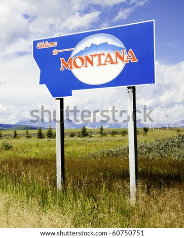 Montana state sign with Rocky Mountains in the distance./ Montana State Sign - stock photo