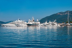 Montenegro.Blue water of the Adriatic Sea.Ships and yachts in the harbor against the backdrop of mountains.
