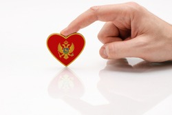 Montenegro flag. Love and respect Montenegro. A man's hand holds a heart in the shape of the Montenegro flag on a white glass surface. The concept of patriotism and pride.