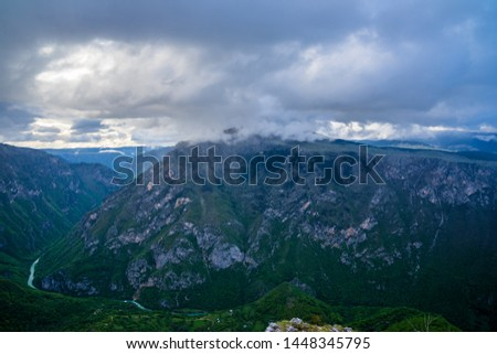 Montenegro, Majestic mountains and ravine of world famous tara river canyon from above a mountain top at dawn in foggy rainy mood in durmitor national park near zabljak #1448345795