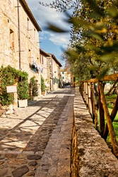 Monteriggioni cobblestone street and ancient architecture with vanishing point. Vertical.