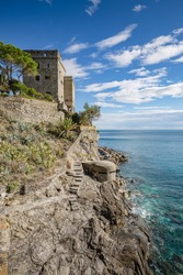 Monterosso al Mare, a coastal village and resort in Cinque Terre, Italy. Way to the small touristic town: stone stairs on the rock wall, tunnel through the mountain and defensive naval bunker