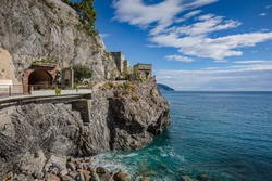 Monterosso al Mare, a coastal village and resort in Cinque Terre, Italy. Way to the small touristic town: stone stairs on the rock wall, tunnel through the mountain.