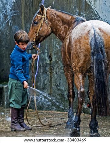 "MONTEVIDEO , URUGUAY  - APRIL 11 :  participant child wash his horse  in the Gauchos show in ""Semana Criolla"", April 11 2009  in Montevideo Uruguay."