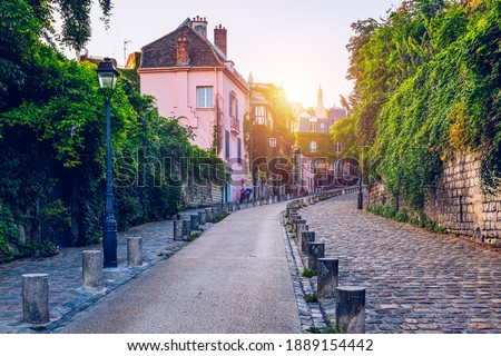 Montmartre district of Paris. Houses on narrow road in Montmartre district of Paris. View of cozy street in quarter Montmartre in Paris, France. Architecture and landmarks of Paris.