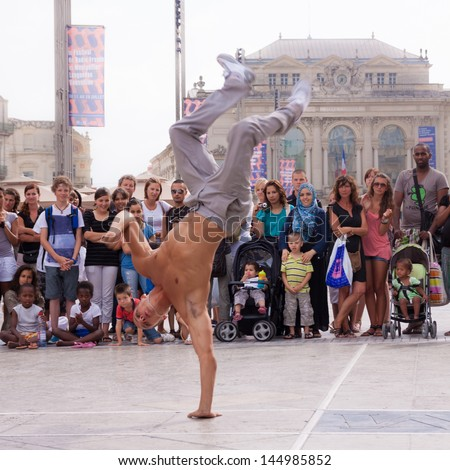MONTPELLIER - JULY 12: Street performer breakdancing in front of the random crowd on July 12, 2011 in  Montpellier, France; B-boying is a style of street dance that originated in NY in early 1970s.