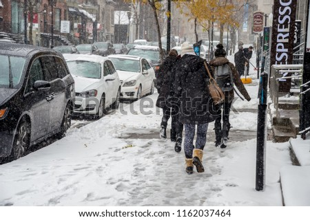 Montreal, CA - 21 November 2016: First snowfall of the season hits the city. Pedestrians in Downtown district. #1162037464