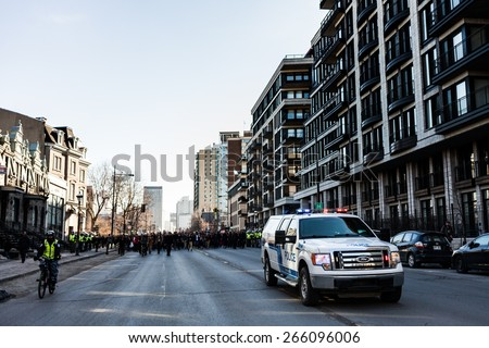 MONTREAL, CANADA   APRIL 02 2015: Riot in the Montreal Streets to counter the Economic Austerity Measures. Police Pick-up Truck in front of the Protesters controlling the Traffic