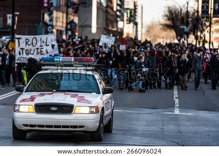 MONTREAL, CANADA   APRIL 02 2015: Riot in the Montreal Streets to counter the Economic Austerity Measures. Police Car in front of the Protesters controlling the Traffic