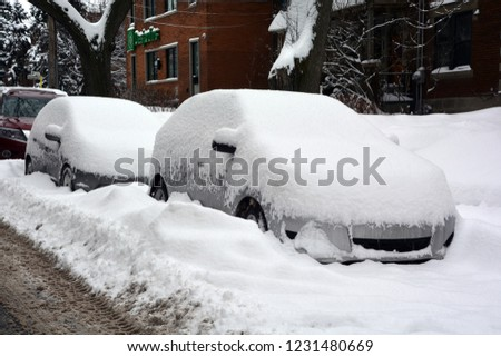 MONTREAL-CANADA DEC. 27 16: Cars cover of snow on Melrose Street. The snow storm slam Montreal with 45 cm of snow after knocking out power to thousands of homes in the U.S. #1231480669