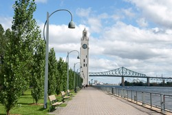 Montreal clock tower located at the entrance of the old port of the city. Also called Victoria Pier or Sailors Memorial Clock. In the background Jacques Cartier bridge.