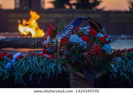 Monument of Great Patriotic War heroes in the Victory park. Eternal fire, flowers around a memorial. Basket with flowers and ribbons.