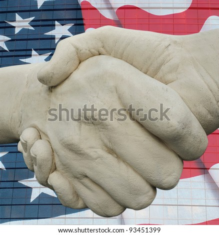 Monument to hand shake against the American flag after which the high-rise building is located
