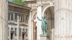 Monument to Roman emperor Constantine I timelapse framed by columns in Milan, in front of San Lorenzo Maggiore basilica. This bronze statue is a modern copy of a Roman statue in Rome.