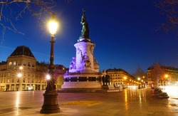 Monument to the republic at night . It is bronze statue of Marianne, a personification of the French republic at the Place de Republique in Paris.