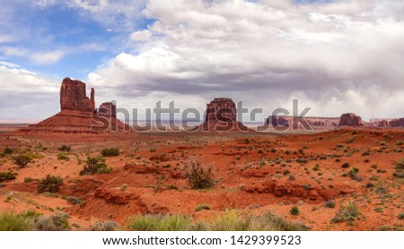 Monument Valley, Navajo Tribal Park in the Arizona-Utah border, United States of America. Red rocks against cloudy sky background #1429399523