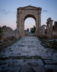 Monumental triumphal arch gate in Tyre Roman hippodrome, with ancient paving stone way leading through ruined columns and buildings, Lebanon, Middle East