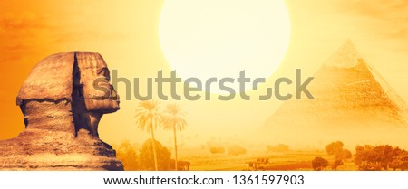 Monuments and ancient symbols of Egypt in a gold sunlight with copy space for text. Wide landscape with Egyptian pyramids, Great Sphinx, Sun and silhouettes of palm trees in Nile valley at sunset.