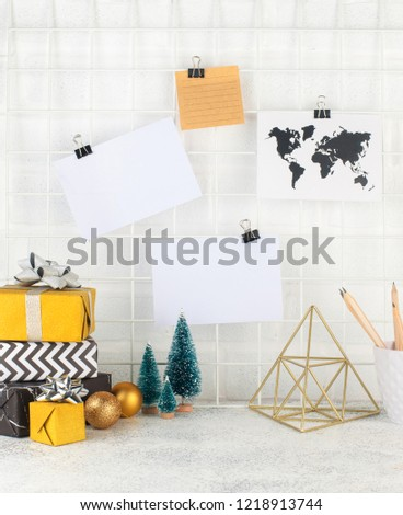 Mood board with empty cards on it near gift boxes and Christmas trees. Blank space for text.