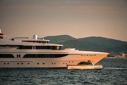 Mood detail shot of Superyacht bow with it's tender chase boat motoring past on a sunset warm light in the bay of Saint-Tropez, South of France