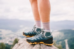 Mood photo of male legs wearing sportive hiking shoes with strong protective sole. Mens legs in trekking footwear for mountain travel standing on stone outdoor at nature on abstract background