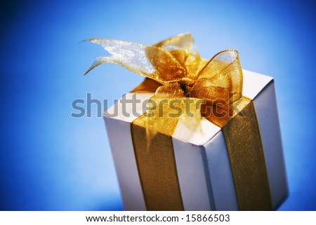 mood shot of luxurious gift box on blue background - intentional selective focus & vignetting