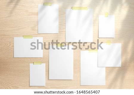 Moodboard template composition with blank photo cards,  polaroid frame glued with yellow adhesive tape on wooden desk with floral shadow overlay.