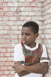 Moody boy leaning against a brick wall, ten years old