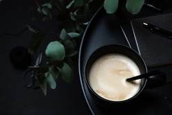 Moody coffee image of latte in black cup with black office accessories on black background with green eucalyptus