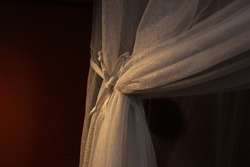 Moody color image of a net curtain tied back by a bow