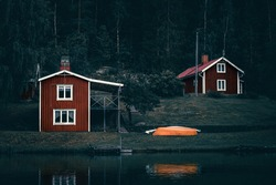 Moody dark swedish houses on a lake at the water