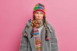 Moody displeased Asian woman concentrated somewhere with offended expression wears knitted hat scarf and grey fur coat poses against pink studio background. Sullen teenage girl in outerwear.