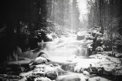 Moody long exposure shot of cascades in the small river Jaran in Bispgarden, Sweden. Light beams are coming from above.