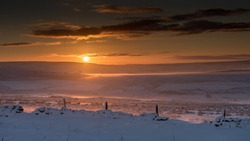 Moody misty sun rise over the Rossendale wintry moorland. Bleak moors covered in snow with a dramatic colourful sky.
