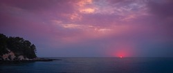 Moody pink and purple sunset seascape over Old Silver Beach in Falmouth on Cape Cod