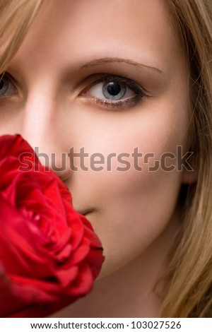 Moody portrait of elegant blonde with big vibrant red rose.