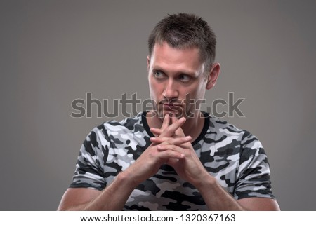 Moody portrait of introspective young man with fingers under chin thinking and looking away on gray background.