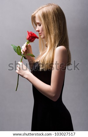 Moody portrait of romantic blond with vibrant fresh red rose.