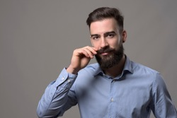 Moody portrait of young stylish bearded man twirling mustache and looking at camera over gray studio background with copyspace.